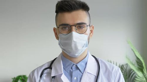 Portrait of A Young Male Doctor Looking into the Camera Wearing a Bathrobe, Bright Room