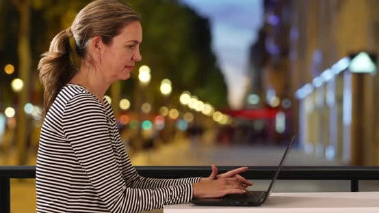 Thumbnail for Side view of businesswoman typing on laptop outside at night