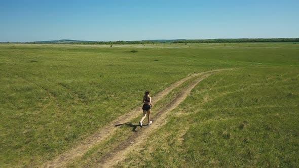 Schlanke Sportlerin läuft auf Pfad in Wiese. Schwenken Sie um Drohne Ansicht von Fit weiblichen Athleten Laufen