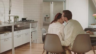 Man Whispering on Ear of Wife in Kitchen