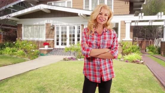 Thumbnail for Fröhliche Frau stehend auf dem Rasen des schönen Hauses lächelnd bei der Kamera