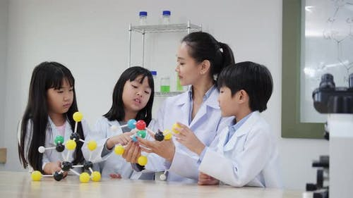 Children studying science about molecules in classroom