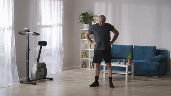 Thumbnail for Middle Aged Man Is Doing Gymnastics at Home at Morning at Weekend Warming Muscles and Joints
