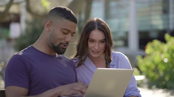 Thumbnail for Man Showing Woman Something on Laptop, Both Looking Involved