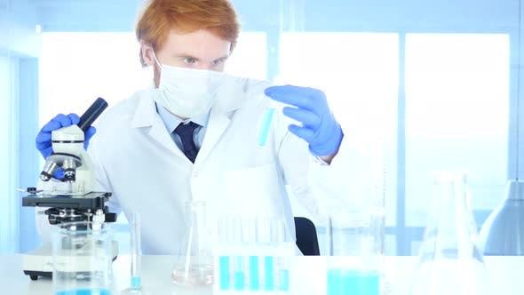 Thumbnail for Scientist Looking at Test Tube Blue Solution and Using Microscope in Laboratory
