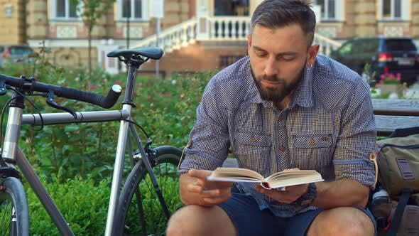 Thumbnail for Cyclist Reads Book on the Bench