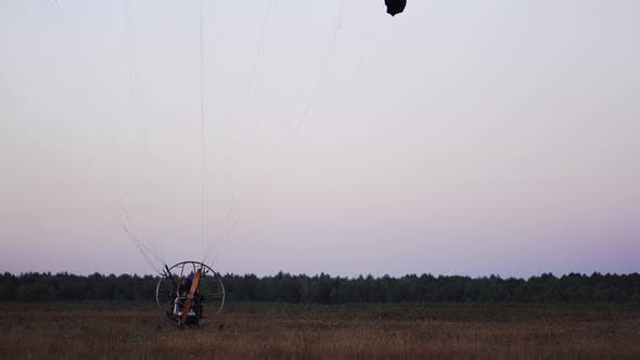Thumbnail for The Motor Paraglider Lowers the Parachute After Landing and Stops Completely in the Field After