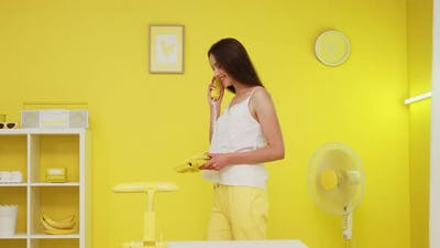 Business Woman Is Talking on Yellow Retro Telephone