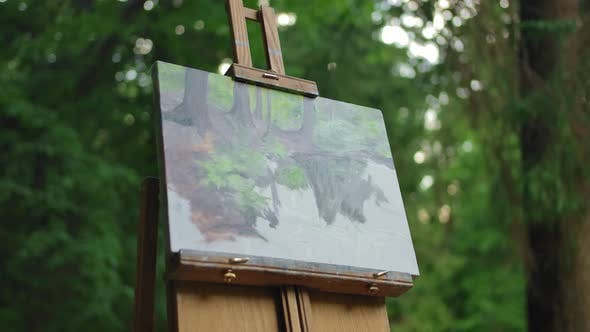 Thumbnail for The Drawing Stands on an Easel in the Middle of the Meadow in a Green Park