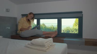 Woman using pad by the window in hotel