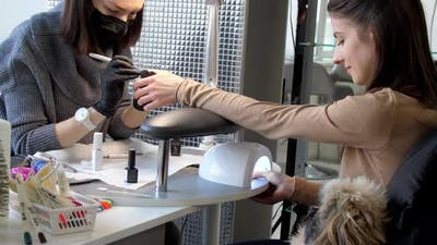 Skilled Manicurist Colours Young Woman Fingernails