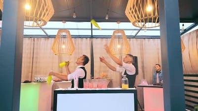 Bartenders Juggling Bottles of Alcohol During a Bartender Show