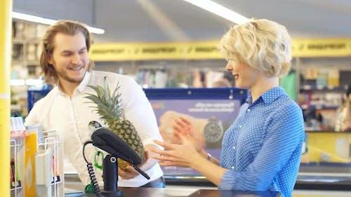 Junges glückliches Paar setzt zahlreiche Produkte zur Zahlung auf Registrierkasse