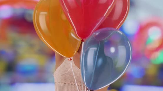 Thumbnail for Laughing Latina cheerfully pops colorful balloons with a pin at theme park