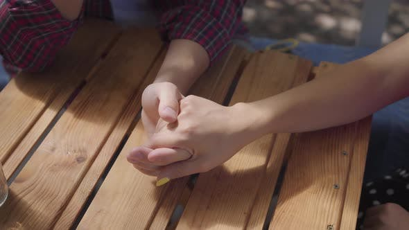 Close-up Hands of Young Happy Couple Sitting Outdoors at the Table Holding Hands