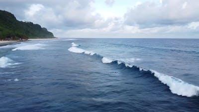 Surfer Dives Under the Wave Fluffy Clouds
