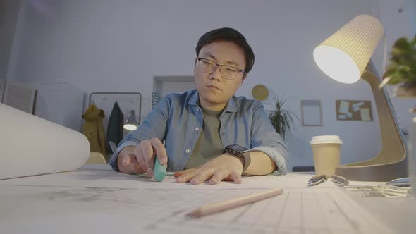Asian Architect Sitting at Office Desk and Drawing House Plan