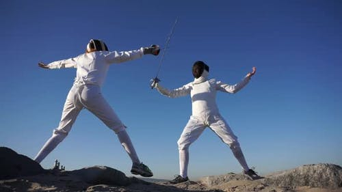 A man and woman fencing on the beach.