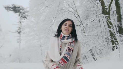 Woman Who Looks Into the Camera on a Frosty Winter Day and Who Walks in a Snow-Covered Forest