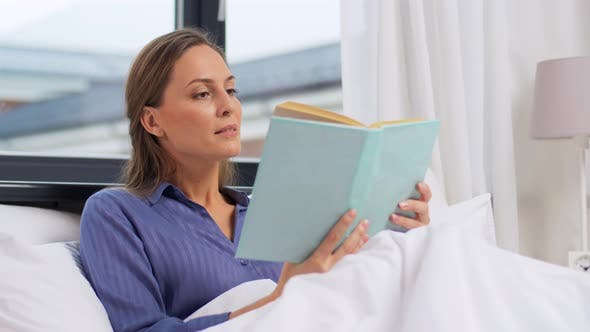 Frau liest Buch und trinkt Kaffee im Bett