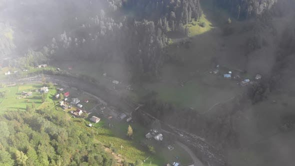Thumbnail for Flying Through the Clouds Over Carpathian Mountain Valley with Village in Summer