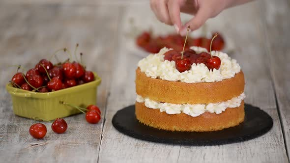 Young Female Confectioner Decorating Naked Cherry Cake.