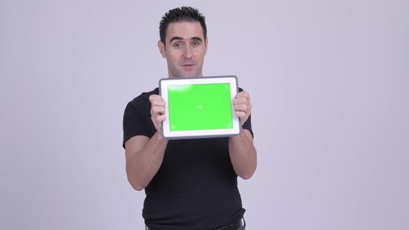 Thumbnail for Happy Handsome Man Showing Digital Tablet Against White Background