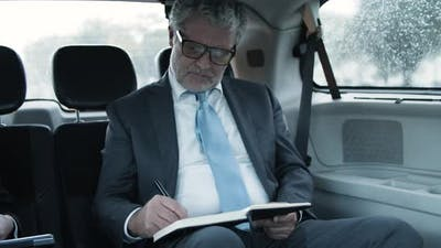 Bearded Businessman Driving in Car and Writing in Notebook