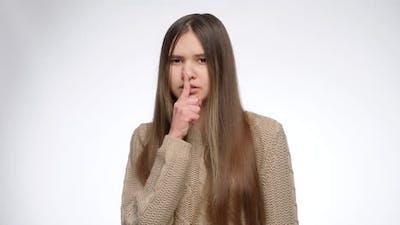Studio Portrait of Girl Holding Finger at Lips