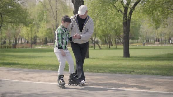 Thumbnail for Grandfather Teaching His Grandson To Ride Roller Skates in the Park