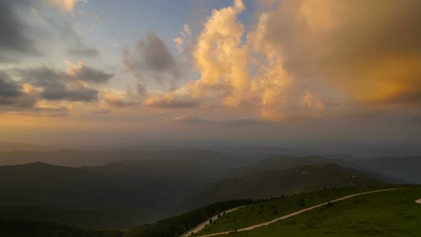 Thumbnail for Time lapse of clouds at sunset over mountain road