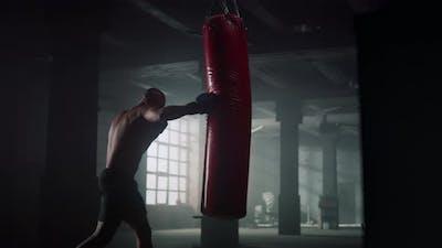 Athlete Hitting Punching Bag in Gloves