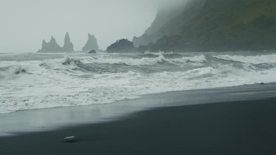 The Black Sand Beach of Reynisfjara with Waves Hitting the Shore on Foggy Rainy Stormy Day