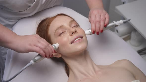 Happy Relaxed Woman Receives a Rejuvenating Cosmetic Procedure at a Cosmetology Center
