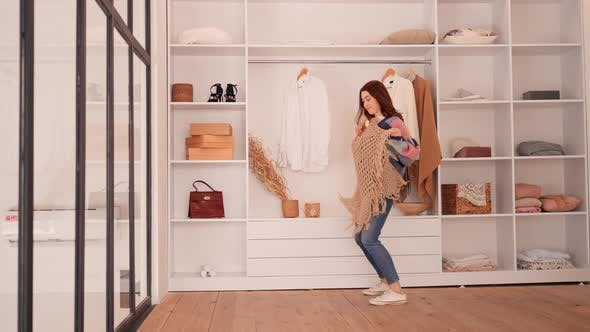 Cheerful Female Trying on Outfits in Wardrobe