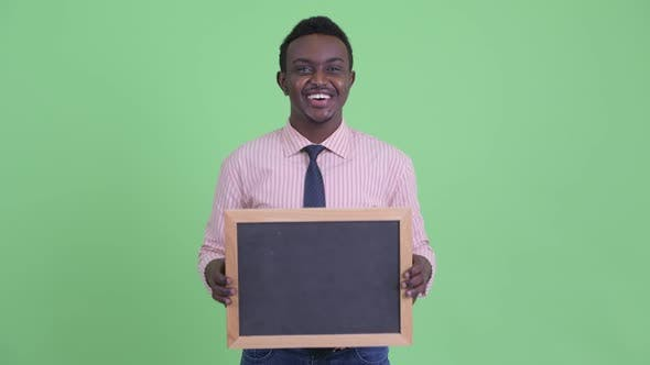 Happy Young African Businessman Holding Blackboard and Looking Surprised