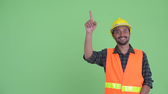 Thumbnail for Happy Young Bearded Persian Man Construction Worker Pointing Up