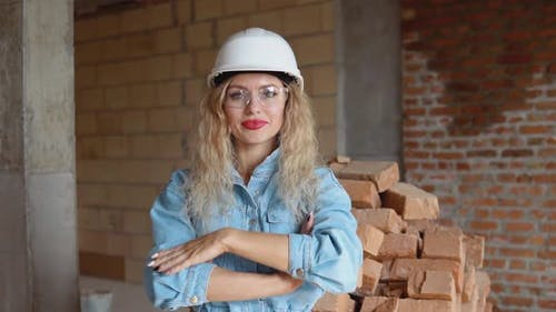 A Young Woman in a Work Helmet and Denim Clothes and Goggles Stands at the Construction Site