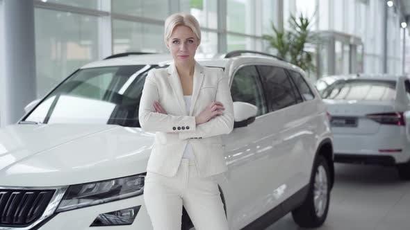 Young Successful Businesswoman in Elegant Suit Posing in Car Dealership