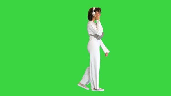 Beautiful Sporty African Girl Listening Music Headphones While Walking Green Screen Chroma Key