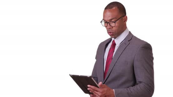 A black executive man does work on his tablet on a white background