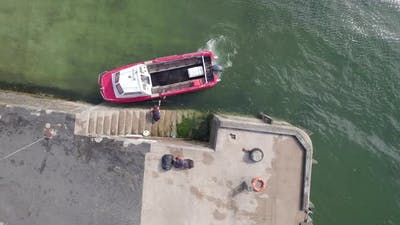 A Small Passenger Ferry Moored on a Jetty Loading Passenger Bags