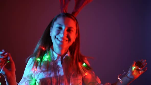 Happy Girl Dancing on a Christmas Party with Christmas Lights Reindeer Attire.