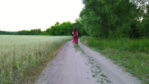 Young Woman with Long Hair in Long Dress Runs on a Field Road, Slow Motion  Shot