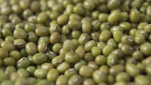 Green Mung beans fall in a pile.