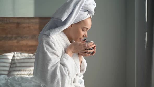Attractive Girl Drinking Tea While Sitting in a Bathrobe and a Towel