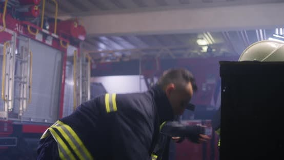 Firefighters Putting on Uniform Near Truck