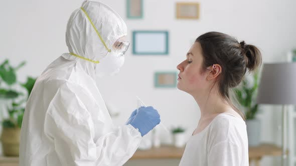 Thumbnail for Healthcare Worker in Protective Suit Taking Nasal Swab from Female Patient