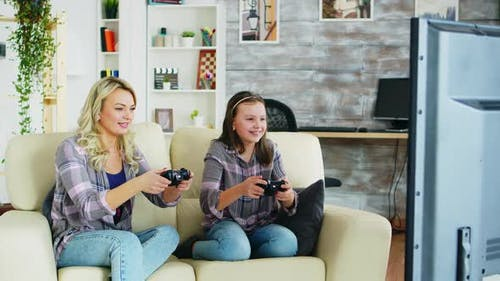 Beautiful Young Mother Playing Video Games with Her Daughter