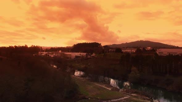 Thumbnail for Fliegen über Fluss und Fabrik bei Sonnenuntergang